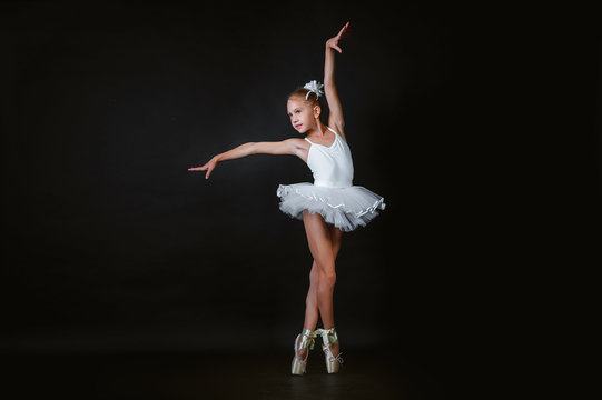 A small young ballerina performs an element of ballet dance on a black background.