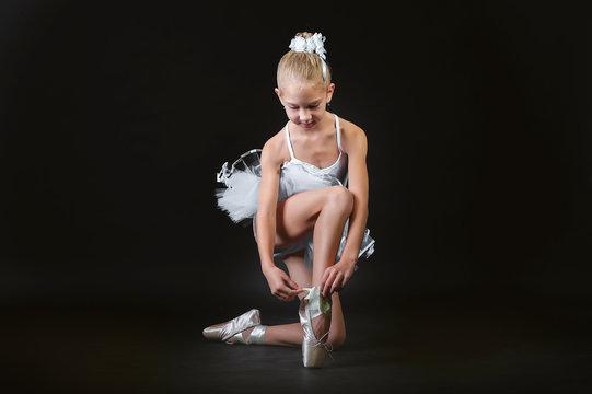 A small young ballerina tie a pointe.