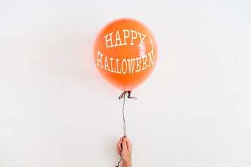 Halloween minimal concept. One orange balloon on white background. Flat lay, top view.