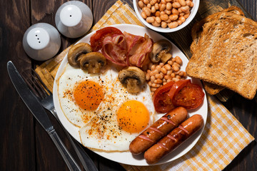 Aluminium Prints Egg Fried eggs with bacon, sausages and vegetables, top view