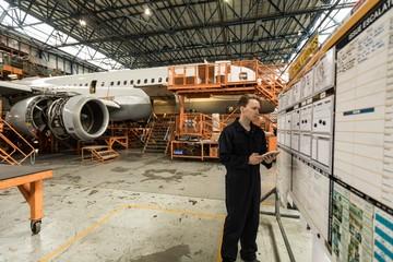 Male aircraft maintenance engineer using digital tablet