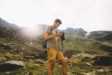 Man browsing camera in mountains