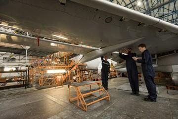 Aircraft maintenance engineers examining aircraft wing