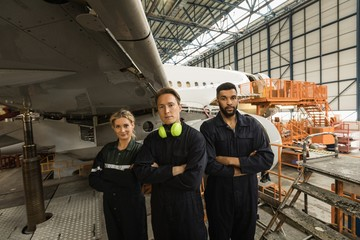 Aircraft maintenance engineers standing with arms crossed at