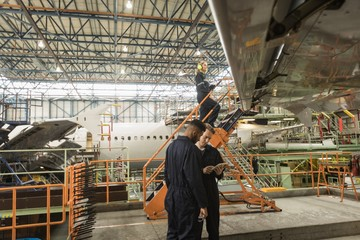 Aircraft maintenance engineers discussing over digital tablet