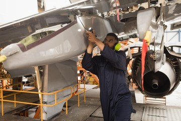 Male aircraft maintenance engineer working over an aircraft