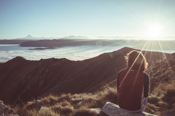 Female hiker reaching her goal at the mountain top and looking at majestic panoramic view of the Alps. Wide angle view at sunset in backlight, toned image, vintage filter, split toning. Wall mural