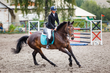 Young girl on bay horse galloping on her course on show jumping training
