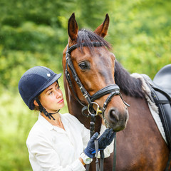 Young smiling rider woman in helmet holding bay horse by bridle