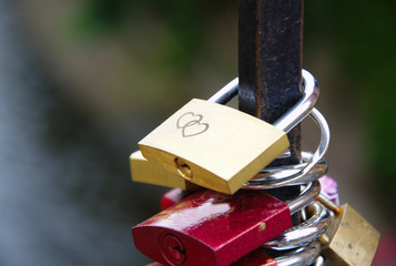 Different colorful locks and one gold with hearts drawing on the bridge fence