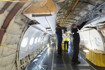 Aircraft maintenance engineers working over internal structure