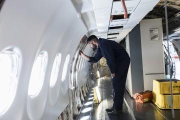 Male aircraft maintenance engineer working over internal