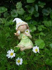 Kleines Zwergenmädchen mit einem Vogel in der Hand sitzt auf einer Blumenwiese