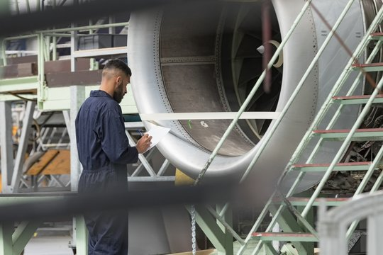 Aircraft maintenance engineer examining turbine engine of