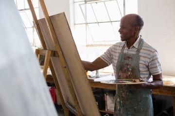 Senior man painting in art class