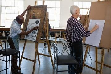 Senior men painting on paper