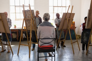Rear view of woman sitting on chair while artist sketching