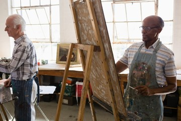 Senior males painting on easel