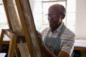Close up of senior man wearing eyeglasses while painting