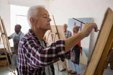 Side view of senior man painting with friends in background