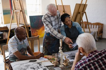 Senior woman discussing over painting with friends