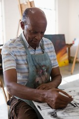 Senior man painting on paper while sitting at table