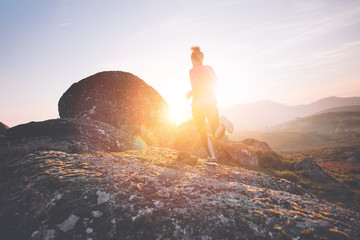 Athletic woman running around in the mountains enjoying the sunset. Sport tight clothes. Intentional motion blur.