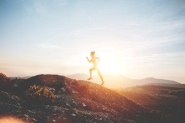 Athletic girl running in the mountains enjoying the sunset. Sport tight clothes.  Intentional motion blur.