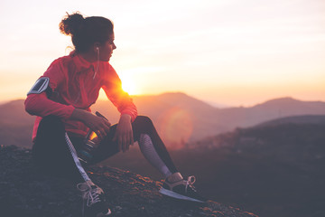 Obraz Athletic woman resting after a hard training in the mountains at sunset. Sport tight clothes. - fototapety do salonu