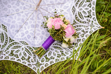 Bouquet of beige roses and pink peonies on a white Bridal umbrella in green grass