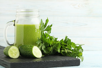 Bottle of juice with parsley and cucumber on white wooden table