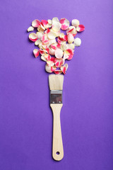 Rose petals and paintbrush on a purple background
