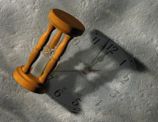 Egg timer and clock face on grey background