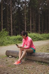 Woman sitting on log and using mobile phone