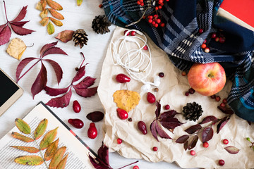 Fresh Pastry Bun, Cup of hot coffee and autumn leaves on wooden background. Wooden letters word AUTUMN. Top view, copy space