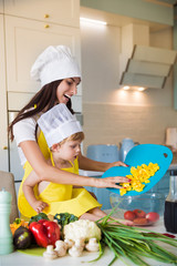 The young cook mother standing with her little son in the kitchen and smiling and putting chunks of yellow pepper in plate