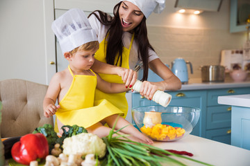 The young cook mother standing with her little son in the kitchen and they salting vegetables