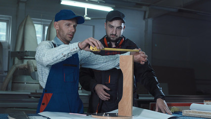 Two men measuring detail and assembling product in carpentry workshop.