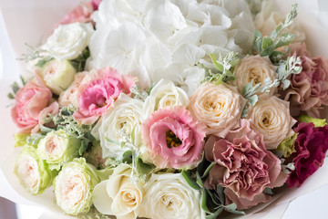 Close-up floral composition with roses and mix flowers on a light background.