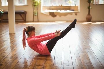 Full length of woman doing yoga on wooden floor