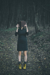 Film photos of girl in a dress with a book in a dark forest - soft selected focus