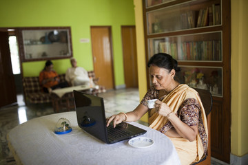 Active aged Indian Woman using Laptop inside home
