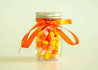 mason jar filled with candy corn tied with orange ribbon isolated on a solid background