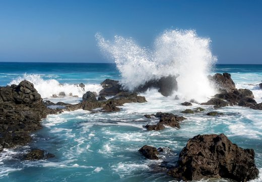 Ocean waves crashing against rocks at Hawaii beach