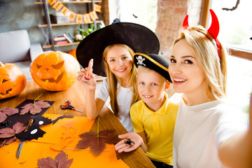 Family portrait of three at halloween party. Happy mom and her cheerful kids - blond small witch and pirate, bonding, lady is making selfie, siblings holding creepy decorations in arm palms