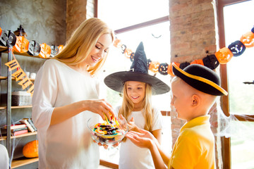 Side profile shot of very excited blond kids in carnival head wear, with treats, attractive blond mommy with bowl of colorful treats, near the window in halloween decorated room indoors at home