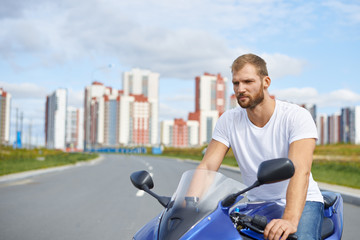 Handsome young biker with beard enjoying street race, riding his blue chopper or motorbicycle and feeling free. Portrait of bearded male model in white t-shirt posing outdoors sitting on motorbike
