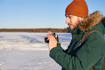 Portrait of serious unshaven young Caucasian adventurer in winter hat and coat setting up his digital photo camera while spending Christmas holidays in wild nature, enjoying beautiful snowy views