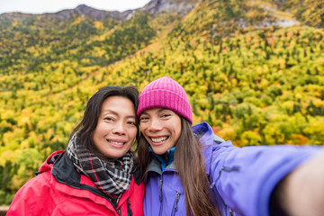 Mother daughter family self portrait selfie women taking picture with smartphone mobile app on outdoor forest hike in autumn nature landscape. Hikers lifestyle.