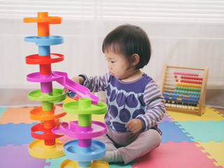 baby girl playing toy at home